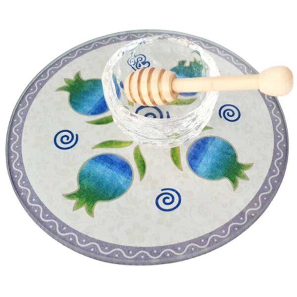 """כלי דקורטיבי מהמם(20 ס""""מ) לדבש. בסיס מזכוכית מחוסמת עם עיטורים ורימונים מהממים בעיצוב יחודי של לילי אומנות כולל צלוחית מקריסטל וכפית מעץ. המוצר מגיע באריזה מכובדת! ישמש כתוספת מכובדת ויפיפייה לשולחן החג."""