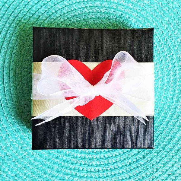 קופסת מתנה מעוצבת בעבודת יד. מלבנית עם קשירות תחרה ולב אדום.
