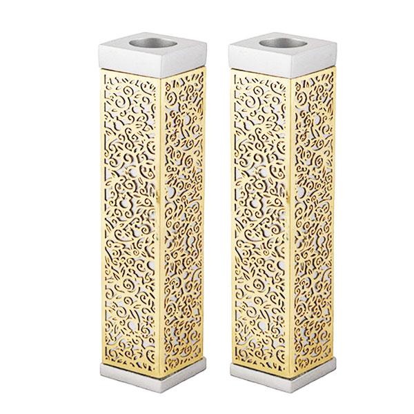 """זוג פמוטים מרובעים גבוהים מהודרים ( 14.5 * 3 * 3 ס""""מ ) אלומיניום ונחושת. עם עיטורי מגזרות מתכת בחיתוך לייזר מדויק המעטרות את הפמוט. גימור זהב. מעוצב ומיוצר ע""""י אמן יאיר עמנואל."""