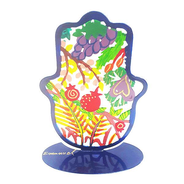 """סטנד חמסה מרשימה ( 15 * 11 * 15 ס""""מ ) ממתכת בחיתוך לייזר צבועה ביד """"7 מינים"""" - יאיר עמנואל. בחמסה זו מופיעים שבעת המינים שנברכה בהם ארץ ישראל כפי שרואה אותה האומן עמנואל בעיני רוחו. החמסה עשויה מתכת בחיתוך לייזר ומצוירת בצבעי אקריליק בציור יד. מחירי מבצע מיוחדים אתר מתנות ישראל"""