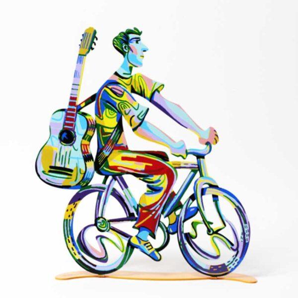 """סטנד """"רוכב עם גיטרה"""" Troubador Rider סטנד מתכת ( 36 * 33 ס""""מ, 0.95 ק""""ג ) צבעוני בעבודת יד עם הדפס דו צדדי על מתכת בחיתוך לייזר. צבעוני ובגימור לכה. סטנד מהמם בצורת הטרובדור רוכב על אופניו עם גיטרה. מעוצב ומיוצר ע""""י האמן דוד גרשטיין. פסל מתכת מקסים זה להנחה על השולחן מדף מאת דייוויד גרשטיין, החוקר את אחד הנושאים החביבים עליו ביותר, רכיבה על אופניים."""