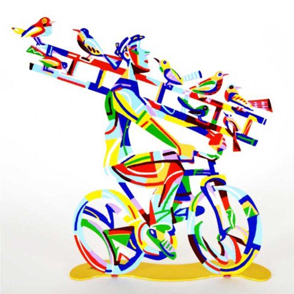 """סטנד """"רוכב עם סולם"""" Ladder Man - סטנד מתכת ( 36 * 36 ס""""מ, 0.9 ק""""ג ) צבעוני בעבודת יד עם הדפס דו צדדי על מתכת בחיתוך לייזר. צבעוני ובגימור לכה. סטנד מהמם בצורת איש הרוכב על אופניו עם סולם. על גבי הסולם ציפורים על גבי הסולם - מעוצב ומיוצר ע""""י האמן דוד גרשטיין. פסל מתכת מקסים זה להנחה על השולחן מדף מאת דייוויד גרשטיין, החוקר את אחד הנושאים החביבים עליו ביותר, רכיבה על אופניים."""
